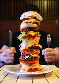 giant burger with person behind it ready to eat