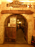 "Make haste to the traditional Romanian restaurant Casa Ardeleana, situatedrather contrastingly in the bowels of the Sora Shopping Centre on ""21 Decembrie 1989"" Avenue. The décor itself is rustic, with wooden panelled walls, decorativebaskets and china, and earthenware cups; the waiters are dressed in traditionalclothing. This, in many other countries, could seem like a tacky gimmick, but the foodmore than compensates (plus they offer free a shot of palinka, traditional fruit brandy, on arrival to sweeten you up). For those willing to whole-heartedly embracetraditional cuisine, have a soup then a main meal; sarmale is the best option for the latter (made from finely pressed cabbage leaves wrapped around meat, onions andspices, served with polenta and ham – it is excellent). However, Brasov Visitor understands that such delicacies are an acquired taste, so available for those of apickier disposition are schnitzel and fried potatoes (chicken and chips a la Romania).Ignore your stomach when it tells you it's in pain; wait half an hour after your maincourse and have dessert. The waiters give excellent advice."