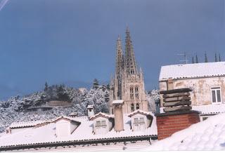 Entre los tejados cubiertos de nieve, asoman dos agujas de la catedral