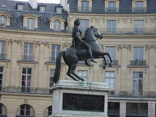 Louis XIV seated on a bucking horse at Place des Victoires. An earlier one showed him on a pedestal supported by four chained prisoners.