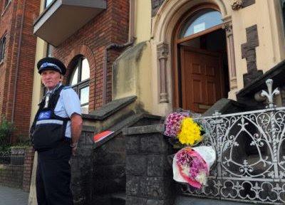 Politiet holder vagt ved opgangen hvor Nancie og Tom Hughes levede