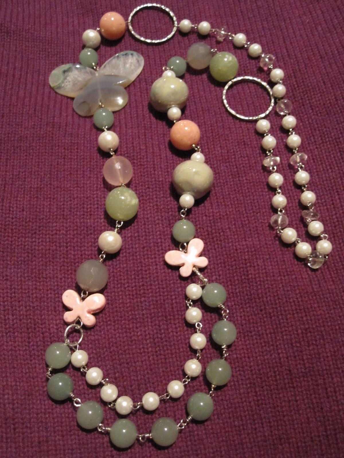 Collar largo en plateado con perlas de dos tamaños, rondeles de cristal de roca, aros redondos, mariposa grande de cuarzo en tonos verde,gris,cristal,