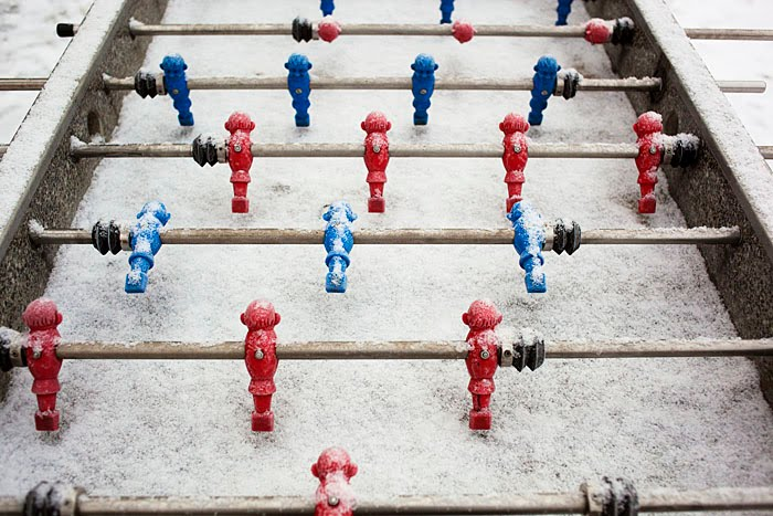 red and blue table football men covered in snow