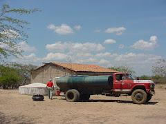 Carro-pipa colocando água em cisterna