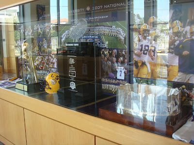 A Smaller Case Near The Center Of Room Holds Teams 2007 National Championship Trophies Including BCS Crystal Football In