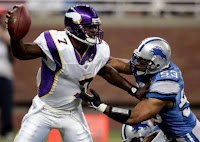 Vikings number 7 holding off a Lions player