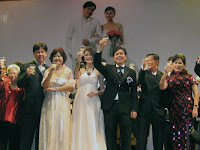 The wedding couple and their parents toasting on stage with their guest