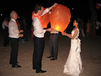 Newlyweds releasing floating lanterns by the beach