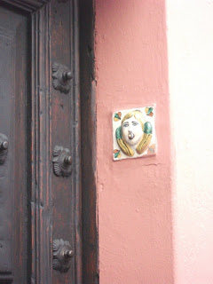 Angled view of the wooden door with the angel-faced ceramic plate for the doorbell