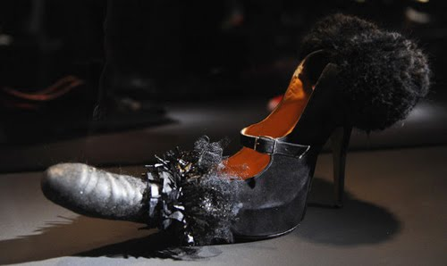 A Vivienne Westwood shoe that is a black pump with ruffles at the back and the front is a penis