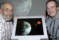 Os astrofísicos suíços Michel Mayor, diretor do Observatório de Genebra e Stephane Udry (D) mostram uma simulação de um novo planeta com as condições de vida semelhantes às da Terra - EFE