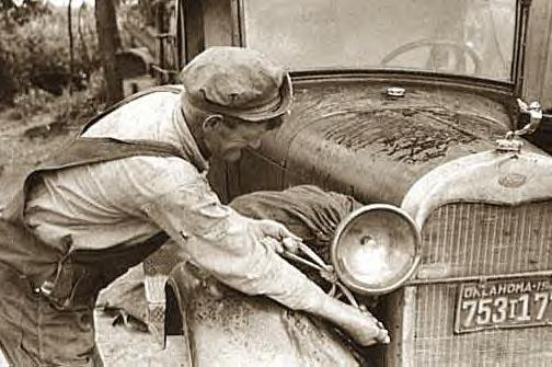 Elmer Thomas tying laundry onto car for trip to Ca., July 1939