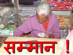 ढिकुरा गाविसको किराना पसलमा एक वृद्धा हिसाब गर्दै