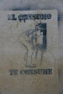 stencil graffiti of a person bending down in front of a tv screen -- their head is inside the screen. Around the image are the words