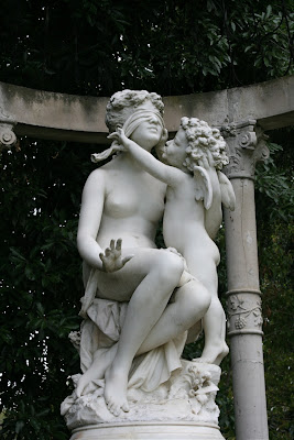 Woman blindfolded by cherub statue