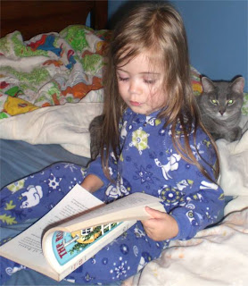 Girl reading book #5 in L. Frank Baum's Oz series, the Road to Oz.