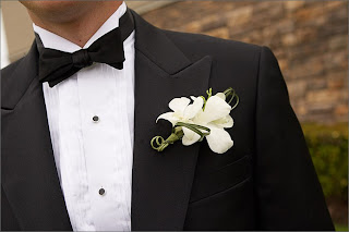 a groom's torso with a flower on his lapel