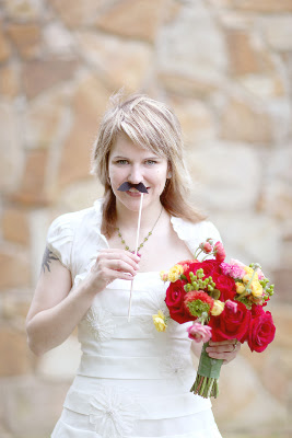 bride holds a mustache on a stick under her nose