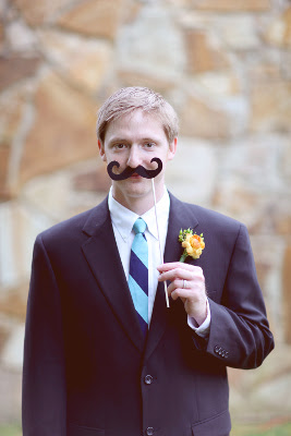man in suit holds a mustache on a stick under his nose
