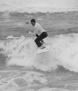 Black and white photo of the groom in dress shirt and black pants surfing