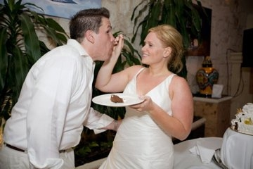 bride feeds groom wedding cake