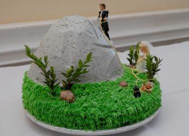 groom climbs up a mountain while the bride is on the ground holding the support line cake