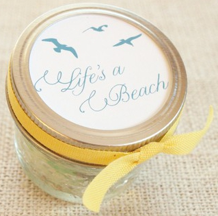 Glass jar with a lid and that says Life's a Beach with a yellow ribbon tied around it