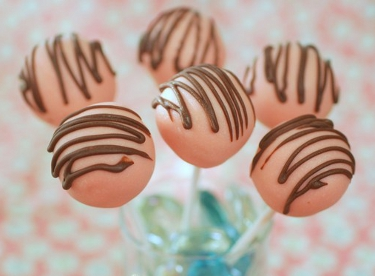 Six pink lollipops with chocolate design on them