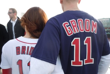 The back of a woman whose white jersey says Bride and the number 11, and a man whose blue jersey says Groom and the number 11