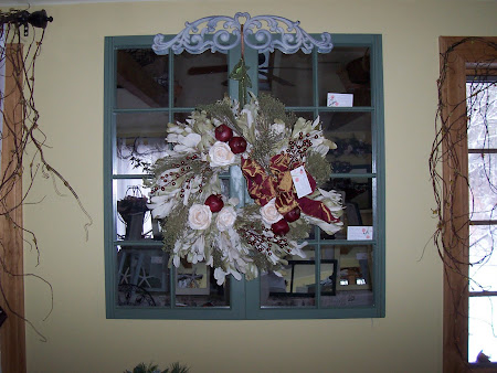 "16-pane sage green mirrored window with a 24"" wreath"