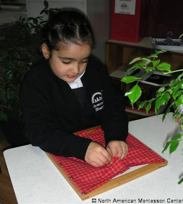 NAMC Montessori Classroom Practical Life Activities girl working with Montessori Dressing Frame