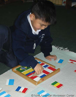 NAMC montessori normalization classroom boy with flag puzzle