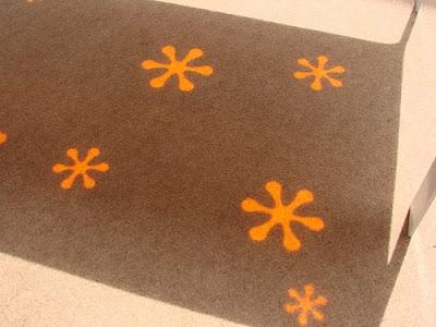 Hoc Die Design, mesa con flores naranjas reflejadas en el suelo