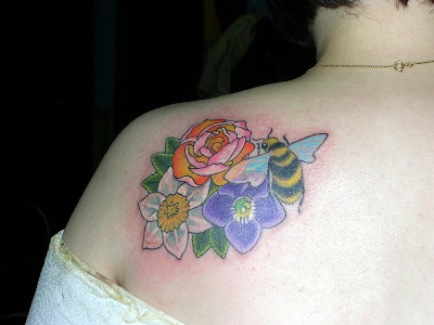 A nice and colorful back of shoulder tattoo of flowers with a bee resting on