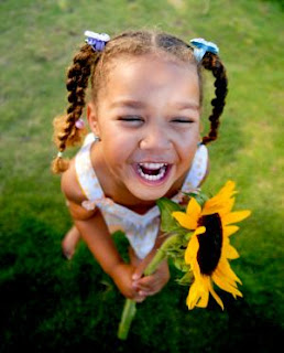 image of child laughing with sunflower
