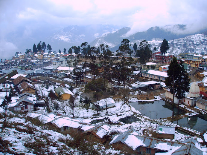 Snowclad rooftops and mountains at Bomdila