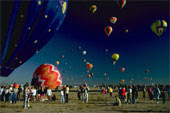 Crowds of people standing at hot air balloon festival as balloons are lifting off, fotosearch.com