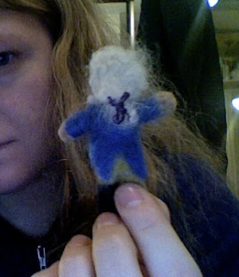 tiny felt George Washington from the back, featuring a ponytail