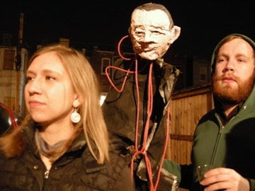 woman and man flanking papier-mache GWBush head on a stick