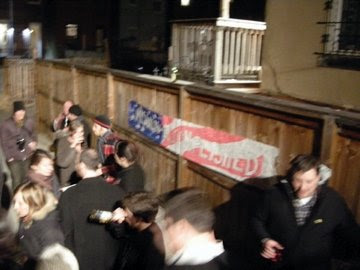 backyard crowed with Mission Accompished banner on a wooden fence