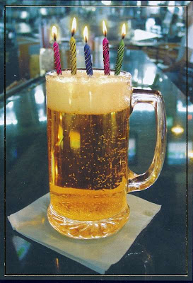 large mug of beer with birthday candles in the foam