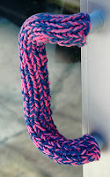 door handle with purple and pink tweed knitted sleeve on it