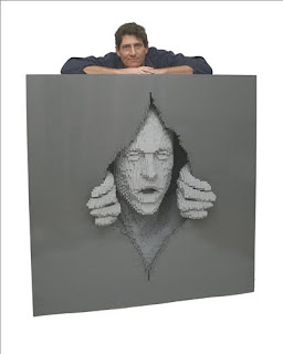 Lego sculpture of hands tearing through a wall with a face peering out, in shades of gray with the sculptor standing behind it