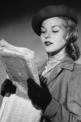 black and white photo of woman reading want adds dressed for job search, circa 1930s