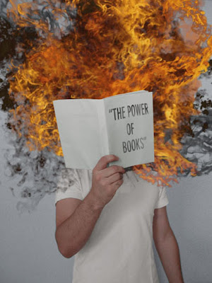 child holding up book entitled the power of books, with flames coming out of it.