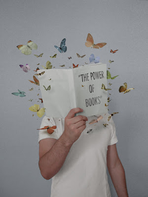 child holding up book entitled the power of books, with butterflies coming out of it.