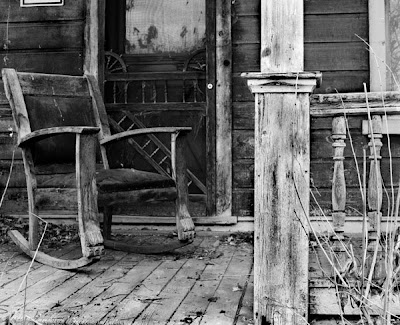 black and white photo of rocking chair on old porch