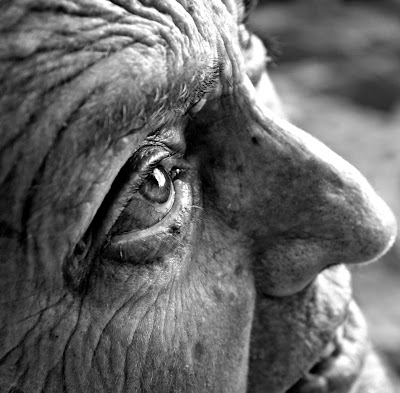 close up on the smiling 3/4 profile of the wrinkled face of an old woman