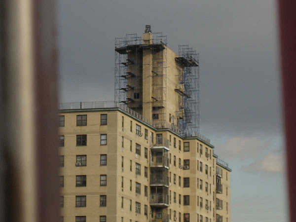 Moody Scaffold - Moody scaffolding on the aircraft carrier con-tower top of a Lower East Side building, seen between the bars of the Williamsburg Bridge.