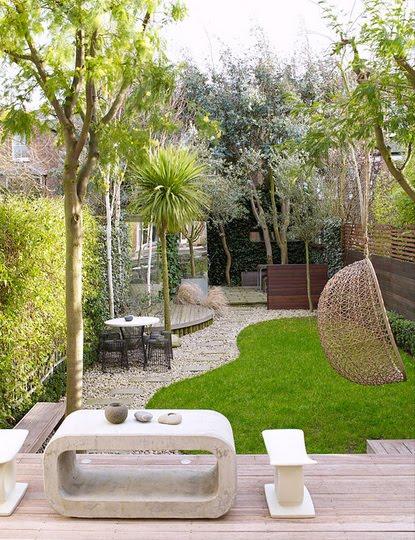 pequeño jardín con tarima madera y silla colgante